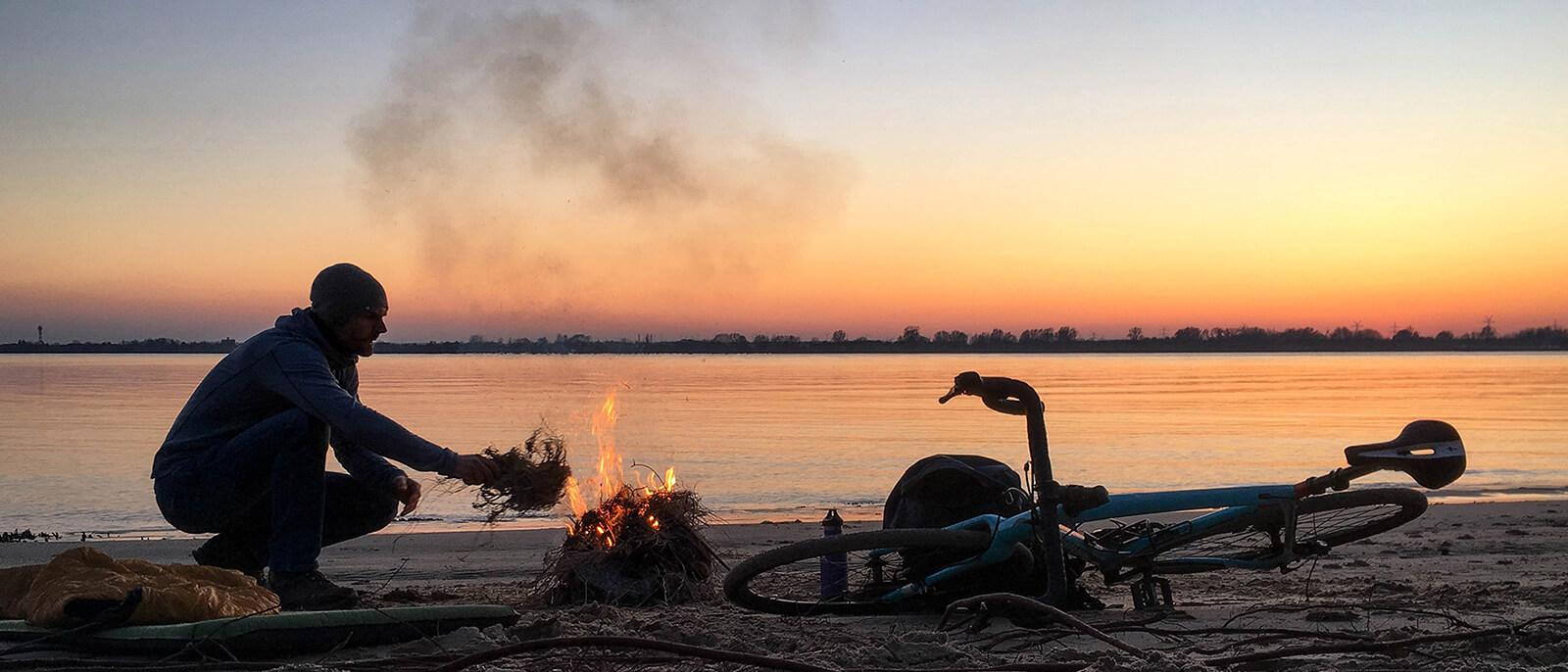 christo foerster mit lagerfeuer am wasser mit fahrrad und schlafsack