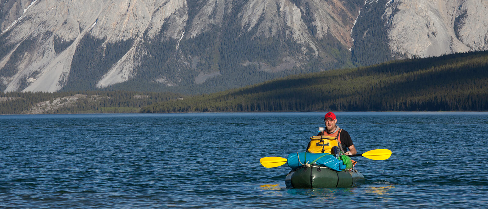robert neu im schlauchboot mit gepaeck im wasser mit paddel in alaska