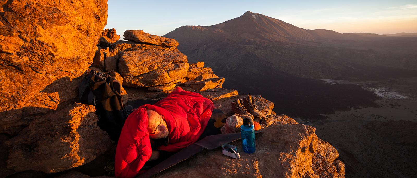 im schlafsack bei sonnenaufgang im gebirge andre schumacher